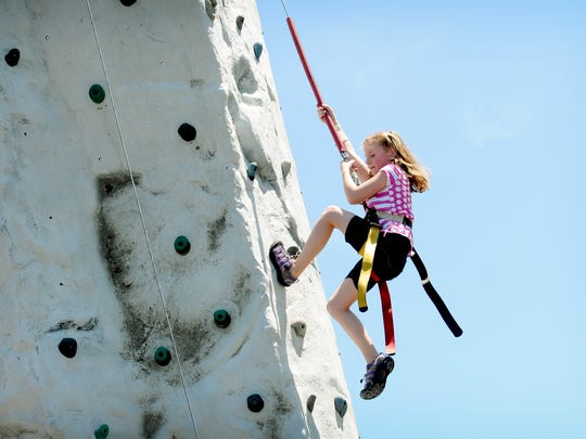 Lillian Graham makes her way to the top of a rock wall