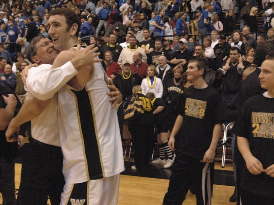 Washington coach Gene Miiller hugs Seth Coy (right) after the Hatchets' win over Memorial in a Class 3A regional game in 2008.