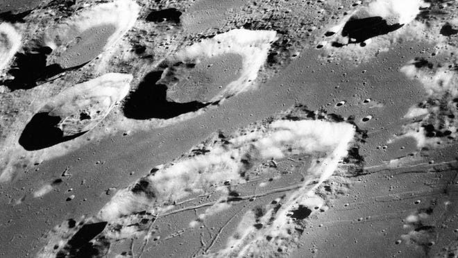 This Dec. 29, 1968 photo shows the large moon crater Goclenius, foreground, approximately 40 statute miles in diameter, and three clustered craters Magelhaens, Magelhaens A, and Colombo A, during the Apollo 8 mission.