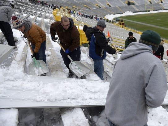 Volunteers shovel snow at Lambeau Field on Monday,