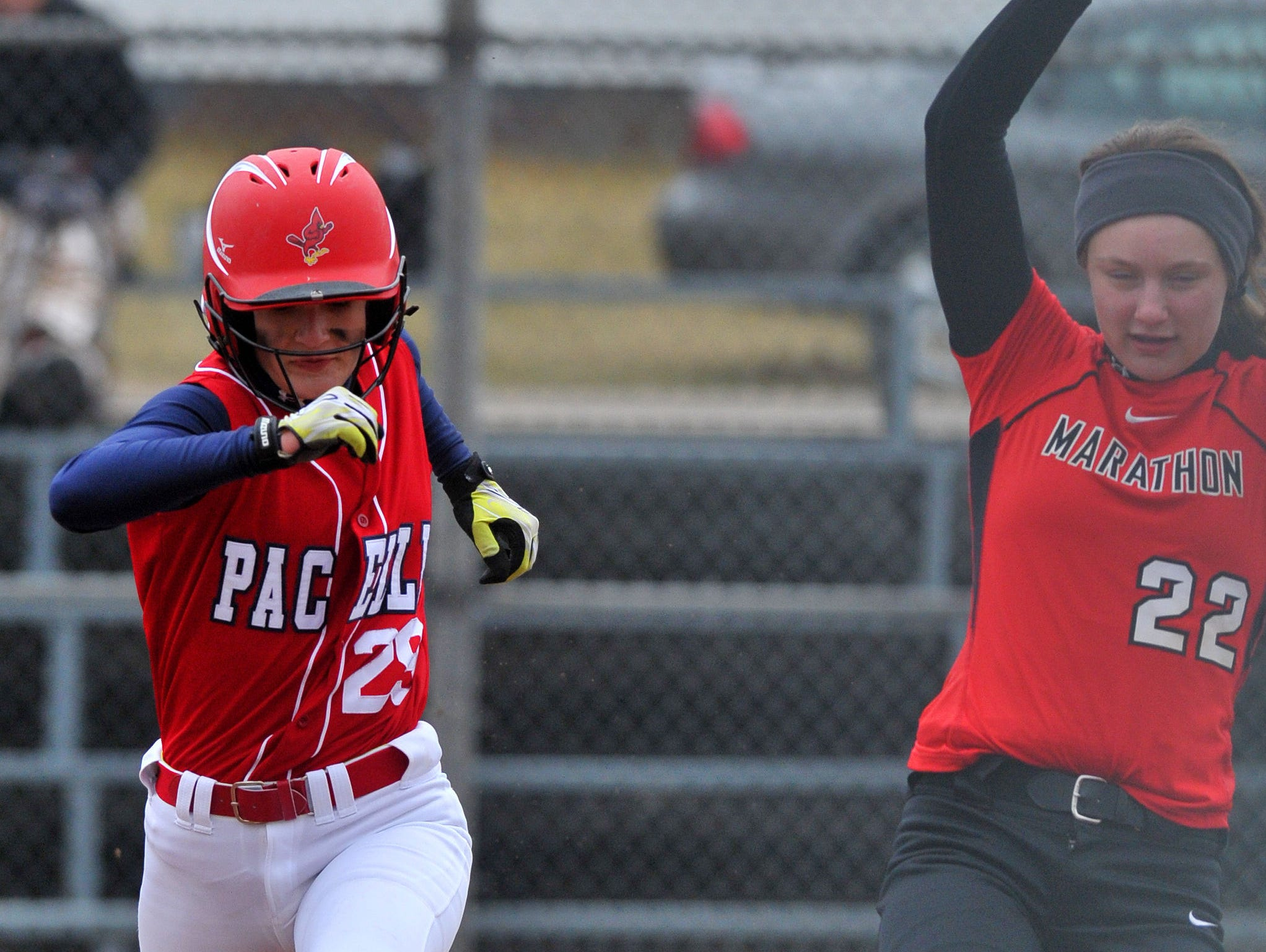 Marathon's Amanda Kind, right, beats Pacelli's Paige Hintz to first base during Monday's nonconference softball game at Marathon.