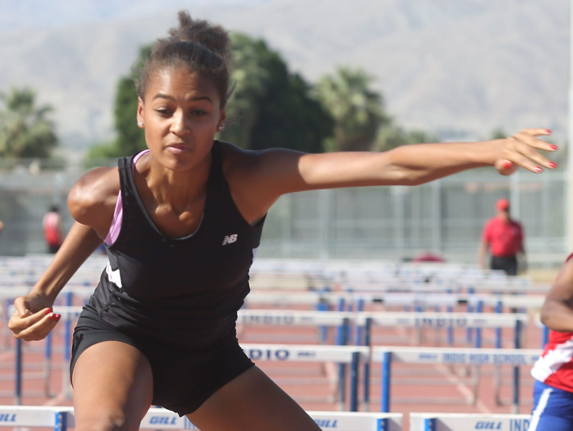 Palm Springs High School freshman Jada McLean wins the 100 meter hurdle race against Indio High School during a track meet between the two schools Thursday.