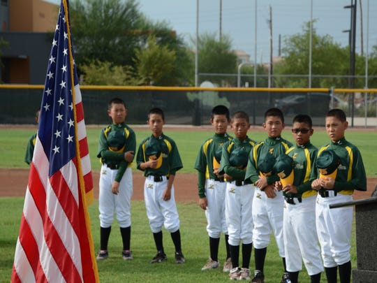 Members of the Tainan City Little League baseball team visiting Chandler stand during the National Anthem at a ceremony on Aug. 12, 2014 at the Diamondbacks Field at the Chandler Boys & Girls Club.
