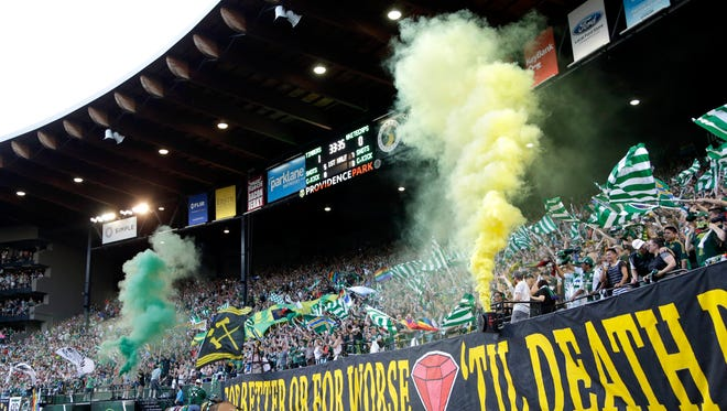 Portland Timbers fans celebrate a goal with colored smoke during the first half of an MLS soccer game against the Vancouver Whitecaps in Portland, Ore., Saturday, July 18, 2015.
