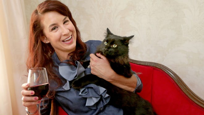 Katy McHugh of Whitefish Bay cuddles with her rescue cat, Sebastian, at her home. McHugh is planning to open Milwaukee's first cat cafe, Sip & Purr, featuring wine, snacks, coffee and adoptable cats this summer at 2021 E. Ivanhoe Place.