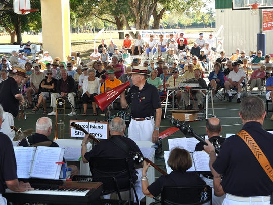 Wes English leads a Mackle Park performance by the Marco Island Strummers, attended by hundreds of traditional music fans.