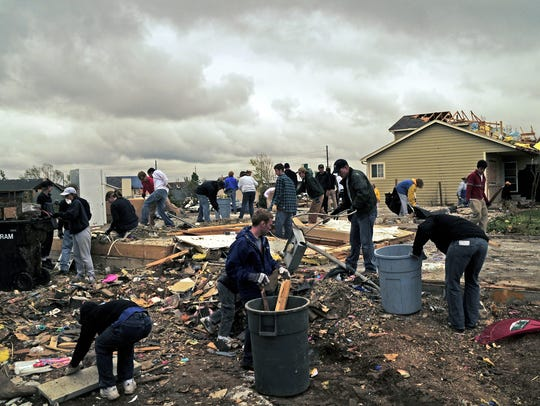People clean up the aftermath of the Windsor tornado