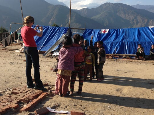 Children gather near a woman taking pictures at a relief camp in Dhunche, Nepal.