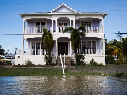 Liza Wells stands on the patio of the second floor of her home in Everglades City looking at the flooding in the street on Sept. 11.