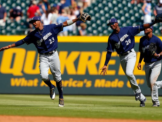 Milwaukee Brewers center fielder Keon Broxton (23) and Lewis Brinson (20) fly in from the outfield as they celebrate the 7-0 victory over the Atlanta Braves in a baseball game, Sunday, June 25, 2017, in Atlanta, Ga. (AP Photo/Butch Dill)