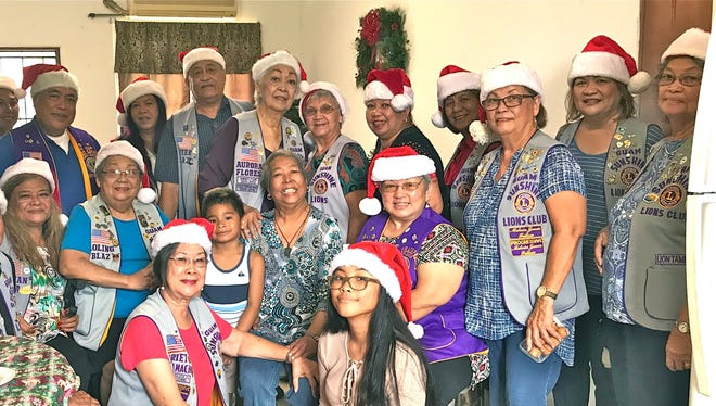 """In keeping with the club's mission of serving and """"Caring for the Sick and the Elderly,"""" club members paid a visit to Cathy Bayona, 55, at her residence in Barrigada on Dec. 16. Members brought supplies, toiletries, song, and cheer to Bayona (front, sixth from left)."""
