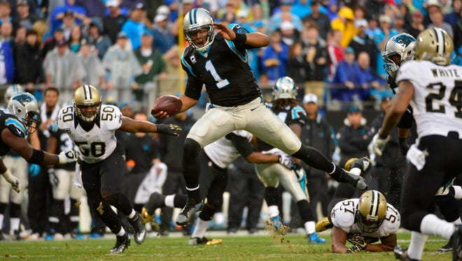 Carolina Panthers quarterback Cam Newton (1) runs as New Orleans Saints middle linebacker Curtis Lofton (50) and outside linebacker David Hawthorne (57) and cornerback Corey White (24) defend in the third quarter. The Panthers defeated the Saint 17-13 at Bank of America Stadium in Charlotte on Dec. 22, 2013.