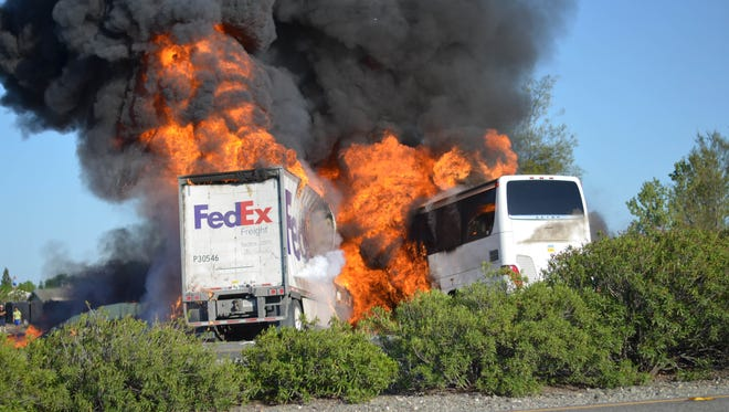 Massive flames are seen devouring both vehicles just after a crash Thursday when a FedEx tractor-trailer crossed a grassy freeway median in Northern California and slammed into a bus carrying high school students on a visit to a college.