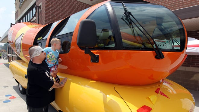 Troy Inman, of Dayton, and his son, Corey, 3, look over the (Oscar Mayer) Wienermobile outside the Kroger store at Newport Pavilion.  The 27-foot-long fiberglass vehicle is built on a Chevrolet truck frame.