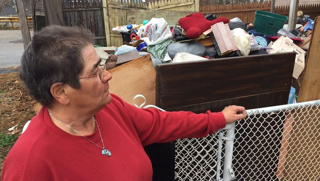 Barbara Hansford stands at the edge of her sister Stella's yard, next to a rental property where garbage has been piled up for about two months.