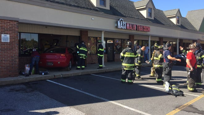 A 25-year-old woman was injured when a car crashed into a Fox Run Shopping Center storefront Friday morning.