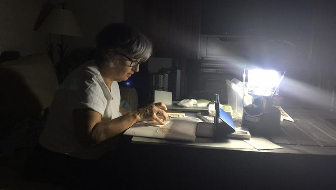 Frances Wagner works on a Stampin' Up project under the light of a Coleman lantern Sunday, Sept. 10, 2017, after she and her husband, Richard, lost power during Hurricane Irma. City utility crews had power restored top their home on Monday.