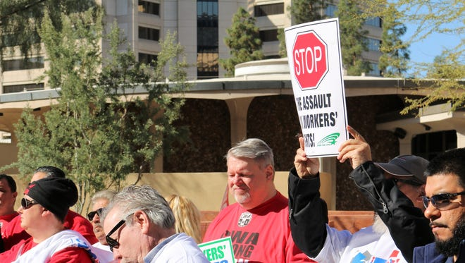 """Retired city worker David Meiner holds a sign that reads, """"Stop the assault on workers' rights!"""" Approximately 50 people gathered Saturday in downtown Phoenix for a Working People's Day of Action rally."""