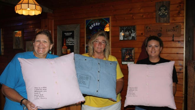 Debbie Teetor, Gina Bell and Nicole Cobb hold pillows made from Henry Nunn's shirts.