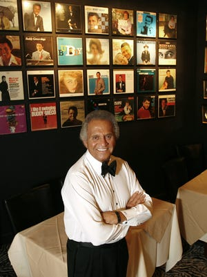 Buddy Greco, shown at his restaurant, Buddy Greco's DinnerClub in Cathedral City. Behind him are  some of his record albums.