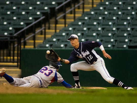 Spring Grove's Dalton Hoiles dives safely back into first base before West York's Brandon Kinneman can apply the tag Tuesday. (For the Daily Record/Sunday News -- Shane Dunlap)
