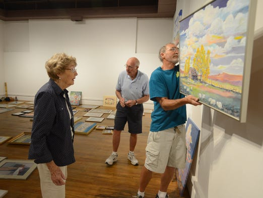 Local artist, Geri Stutheit, left, looks while her son, Paul, hangs one of her paintings at the Community Creative Center Monday July 7, 2014, as she and her family hang her work for a retrospective show about the 50-plus years of work as an artist. The show opens to the public on Thursday July 9. In the background is her husband, Wilbur.