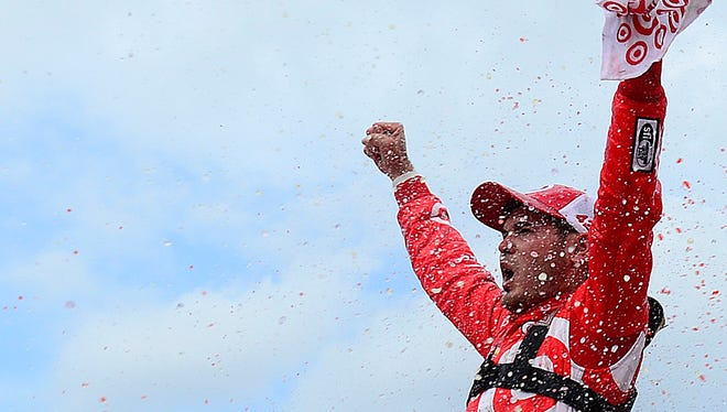 Kyle Larson, driver of the No. 42 Target Chevrolet, celebrates in victory lane after winning the NASCAR Sprint Cup Series Pure Michigan 400 Sunday at Michigan International Speedway.