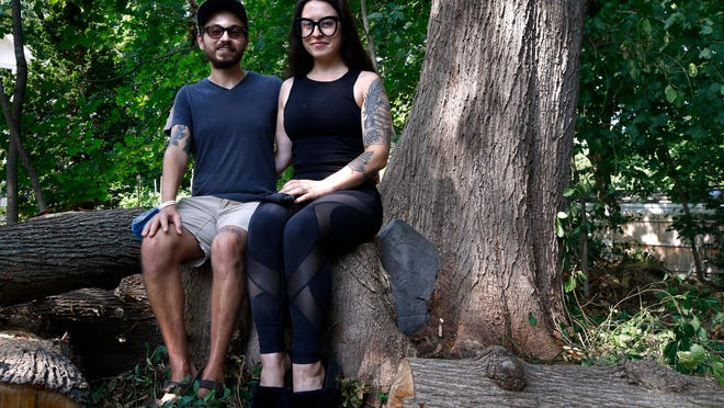 Christopher Mongeau and Allison Palombo on the stump of one half of a double tree in their yard in Hopkinton, R.I., with a mysterious presence -- the pentagonal grave marker -- just to the right of Palombo.