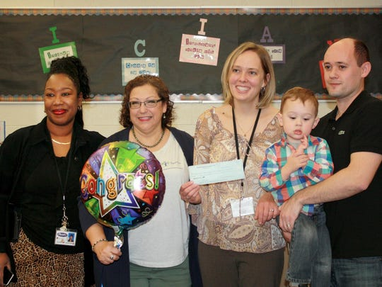 (From left) Shawndra Hernton, Beechview Elementary School principal, and Linda Wozniak, Shepard Insurance AgencyrRepresentative, pose with Rachel Moore, classroom makeover winner, along with Moore's husband and son.