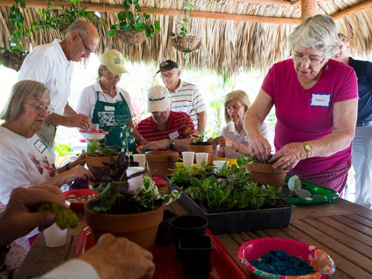Marion Southard, right, uses plants and accessories to create a potted nature scene during a therapeutic horticulture program in the Buehler Enabling Garden at the Naples Botanical Garden on Tuesday, April 18, 2017.