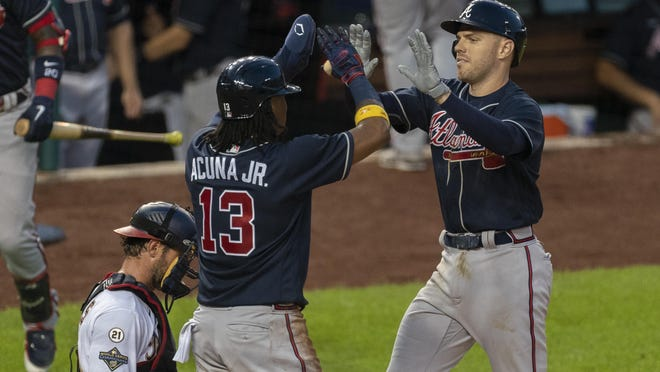 Atlanta Braves' Freddie Freeman, right, is congratulated at home plate by teammate Ronald Acuna Jr. (13) next to Washington Nationals catcher Yan Gomes, left, after hitting a two-run home run during the fourth inning of a baseball game in Washington, Thursday, Sept. 10, 2020.