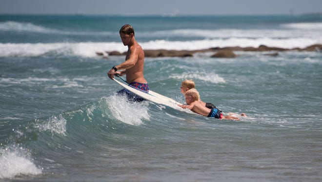 """Michael Molina, of Stuart, prepares his sons, 4-year-old Marin and 1-year-old Mehrk, to catch a wave between Bathtub Reef and the shore Thursday, April 26, 2018, in Martin County. """"Normally it drops off deep and it's not safe for kids,"""" Molina said, referring to the reef, """"but now we got this sandbar where it gradually gets deeper."""" He said since a dredge operation was moved to Jensen Beach, sand has flowed down to fill in the area."""