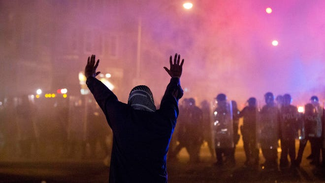 A protestor faces police enforcing a curfew Tuesday, April 28, 2015, in Baltimore. A line of police behind riot shields hurled smoke grenades and fired pepper balls at dozens of protesters to enforce a citywide curfew.