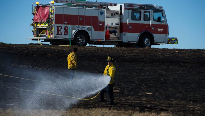 Firefighters douse the last of a grassfire on Friday, March 16, 2018, at the northeast corner of Interstate 25 and East Mulberry Street in Fort Collins, Colo.