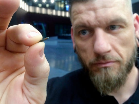Jowan Osterlund from Biohax Sweden holds a small microchip implant in this file photo.  A state representative from Greenbrier has introduced legislation that would require employers to receive written approval from employees before outfitting them with microchips.