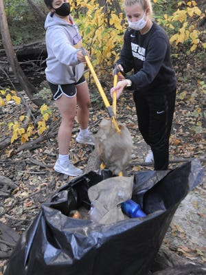 Kansas Wesleyan students Chelsea James, left, and Jessica Vegely picks up trash in the river channel by the Salina Family YMCA during last year's Fall Fix-Up event. Picking up trash along the Smoky Hill River Channel is one of eight opportunities during this year's event.
