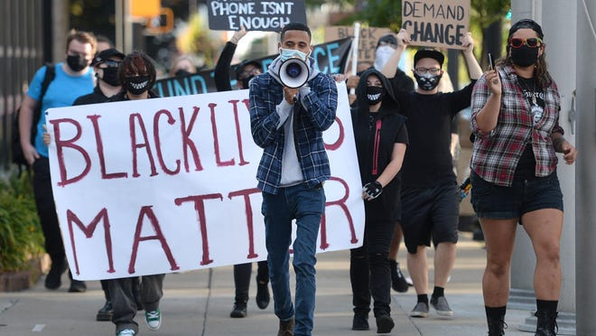Erie Equal founder Andrey Rosado, center, leads protesters as they march past Erie City Hall during the We Will Not Stay Silent rally on Aug. 29, 2020. The rally, organized by Erie Equal, was in response to the social unrest and violence in Kenosha, Wisconsin and other cites across the country.