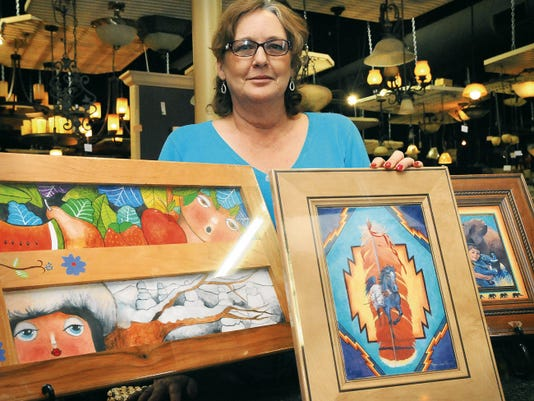 """Kitchen Kraft owner Stephanie McDaniel stands with painted doors created by local artists for """"Opening Doors,"""" a Tutti Bambini benefit for borderland children's charities silent auction next week that concludes with a reception at 5 p.m. on April 17."""