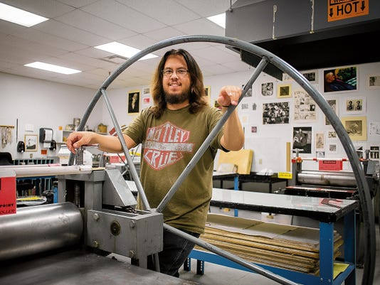 NMSU graduate student Joshua Flores stands by a printing press on the second floor of D.W. Williams Hall. He has recently delved into print making, broadening his ability to express himself even further.