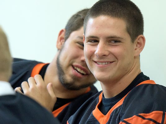 Northeastern player David Ankney shares a thought with teammate Gary Gobernik during York-Adams Football Media Day at the York Newspaper Company on Monday. The Northeastern football team has dedicated the 2015 season to senior quarterback Marcus Josey, who was diagnosed with a form of leukemia in April.