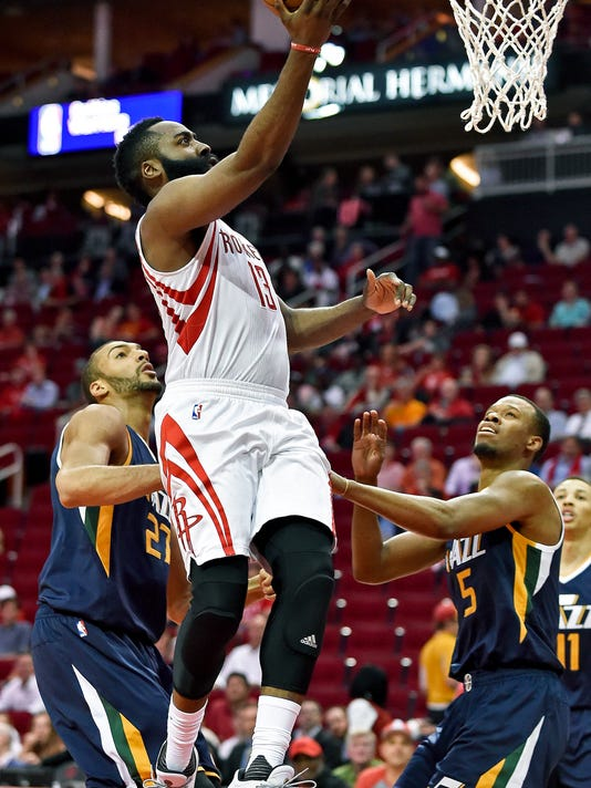 Houston Rockets guard James Harden (13) shoots over Utah Jazz center Rudy Gobert, left, and guard Rodney Hood in the first half of an NBA basketball game, Wednesday, March 8, 2017, in Houston. (AP Photo/Eric Christian Smith)
