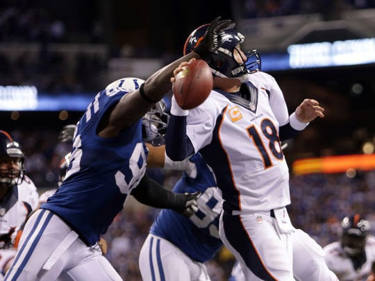 Denver Broncos quarterback Peyton Manning, #18, is hit from behind by former teammate Indianapolis Colts Robert Mathis, #98, Sunday, October 20, 2013.  Robert Scheer/The Star