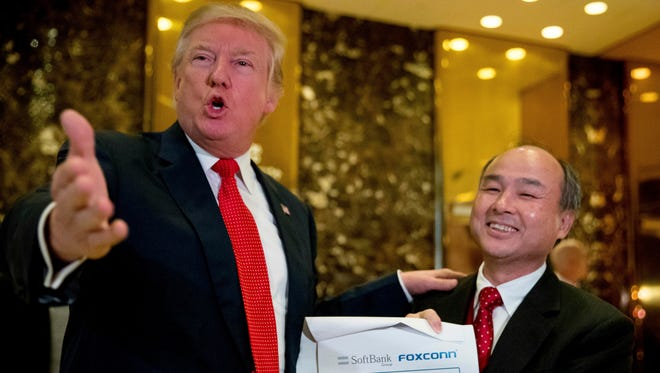In this Tuesday, Dec. 6, 2016, file photo, President-elect Donald Trump, left, accompanied by SoftBank CEO Masayoshi Son, speaks to members of the media at Trump Tower in New York. Trump talked up Japanese mogul Son, who after meeting with the president-elect in New York, spotlighted his plan to invest $50 billion and create 50,000 jobs.