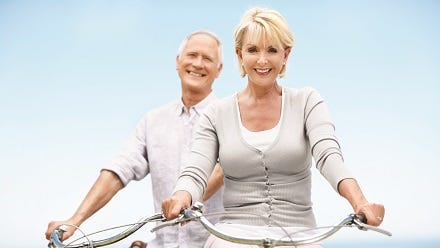A happy mature couple setting off on their daily bike ride.