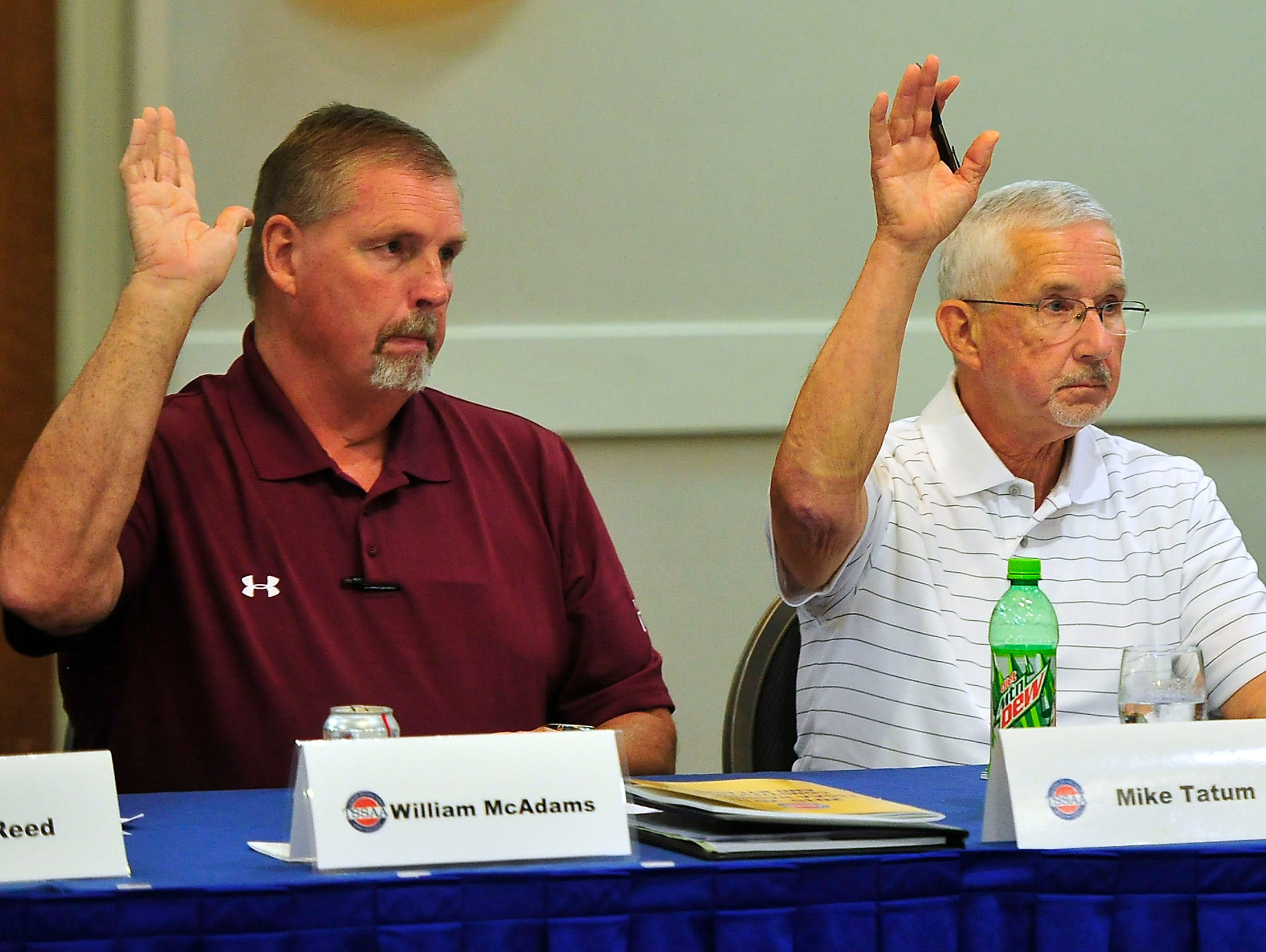 William McAdams, left, and Mike Tatum, center, vote on one of seven proposed changes as Danny Gilbert looks on during a TSSAA Legislative Council meeting at DoubleTree Hotel in Murfreesboro, Tenn., Tuesday, Sept. 1, 2015.