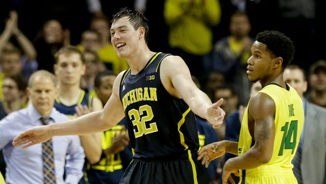 Michigan's Ricky Doyle (32) and Oregon's Ahmaad Rorie (14) react during the second half of an NCAA college basketball game Tuesday, Nov. 25, 2014, in New York. Michigan won the game 70-63.