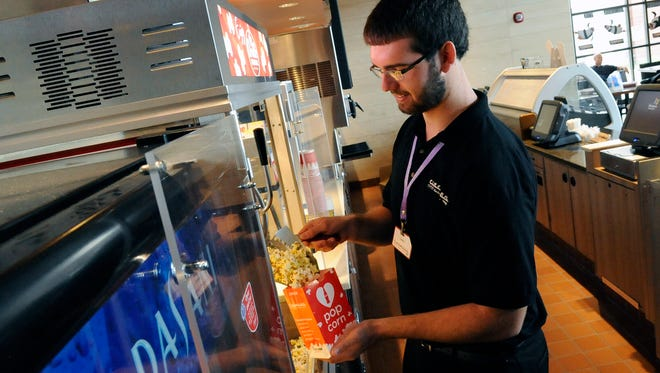 James Vallenger fills a bag of popcorn Wednesday at Cinemark Theater in Lancaster. The new movie theater will open to the public on Friday.