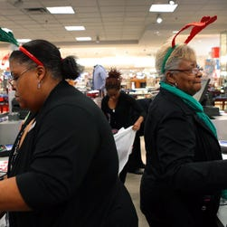Macy's sales associates Vanessa Robinson, left, and Augustine Brooks attend to shoppers at the checkout counter in the St. Louis, Mo., Galleria. Clerks will likely be just as busy with returns after Christmas as they were before the holiday.