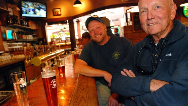 In this Nov. 19, 2014 photo, regulars Jerry Christensen, left, and Bob Brubaker enjoy their favorite beers at Deschutes Brewery's brew pub in Bend, Ore. As Bend has grown from struggling timber town to outdoor recreation destination, its breweries have grown with it. After opening in 1988 as Bend's first craft brtewery, Deschutes now distributes coast-to-coast, and many of its brewers have left to start their own breweries. (AP Photo/Jeff Barnard)