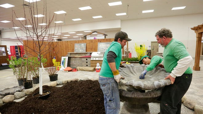 Ryan Kissel, Luis Chic and Scott Franke of Stuart's Landscaping & Garden Center set up a fountain at the Fond du Lac Expo Center in preparation for the Super Home Extravaganza, starting at 4 p.m. Friday.